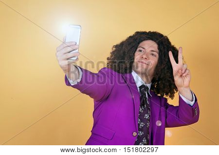Caucasian man with afro wearing Purple Suit taking a selfie