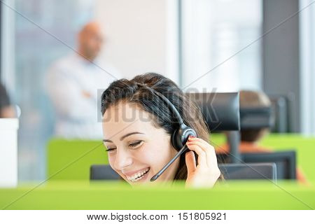 Smiling young businesswoman using headset in office
