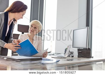 Businesswomen discussing over new project at desk in office