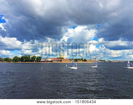 View on Peter and Paul Fortress in Saint Petersburg. Tiny boats and Neva river in the forefround. Summertime.