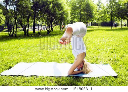 blonde real girl doing yoga in green park, gymnastic head over hills outside, lifestyle sport people concept close up