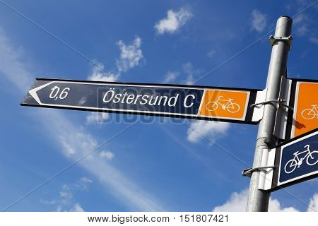 Signpost with distance and direction to the railway station in the Swedish town Ostersund for bicicle riders.