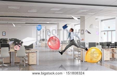 Dancing businessman in office room . Mixed media