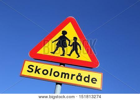Swedish road sign against blue sky Warning for Children - School zone.