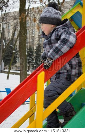 Cute child climbing down ladder on colorful little house at playground