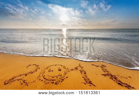written 2017 on the beach, golden sands and blue sky