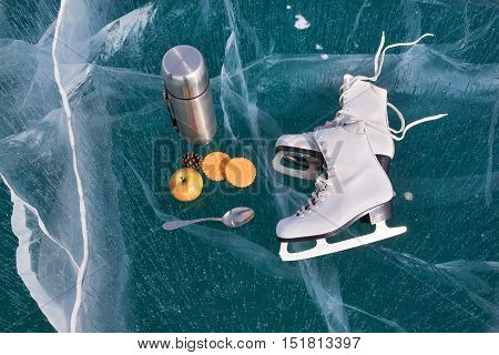 Ice skates at transparent cracked ice surface with snack. thermos biscuits apple and spoon. Winter sport concept. Lake Baikal ice.