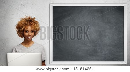 Beautiful Dark-skinned Young Female Teacher With Stylish Haircut Checking Papers Of Her Students, Us