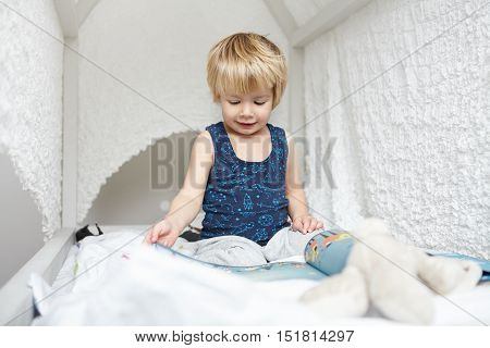 Portrait Of Beautiful Caucasian Baby Boy With Fair Hair Dressed In Pajamas Sitting On White Canopy B