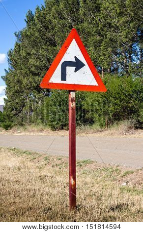 Rural turn sharp right traffic sign next to rural road