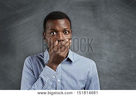Astonished Bug-eyed Dark-skinned Student Wearing Checkered Shirt, Covering His Mouth, Looking Shocke