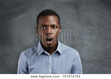 People And Education Concept. Portrait Of Handsome African Student With Bugged Eyes And Mouth Wide O