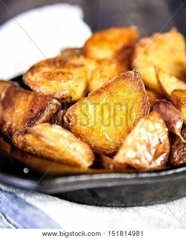 Delicious hot baked potato wedges with garlic in black rustic plate on kitchen towel. Appetizing crisp. Traditional garnish or side dish for Christmas dinner. Country-style roasted potatoes