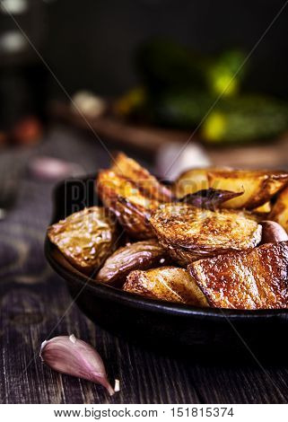 Delicious baked potato wedges with garlic in black rustic plate on kitchen towel. Pickled cucumbers behind. Traditional garnish or side dish for Christmas dinner. Country-style roasted potatoes