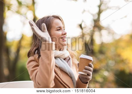season, hot drinks and people concept - beautiful happy young woman drinking coffee or tea from disposable paper cup and waving hand in autumn park