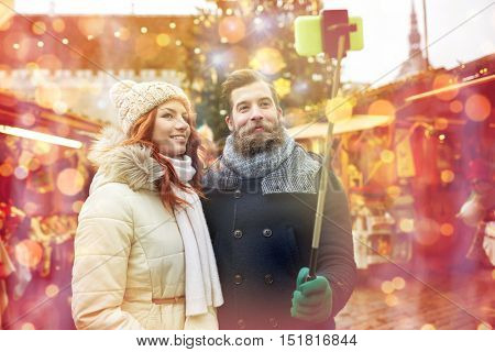 holidays, winter, christmas, technology and people concept - happy couple of tourists in warm clothes taking picture with smartphone selfie stick in old town