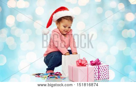 childhood, christmas, holidays and people concept - happy smiling little african american baby girl in santa hat with gift boxes playing with confetti and shopping bag over blue lights background