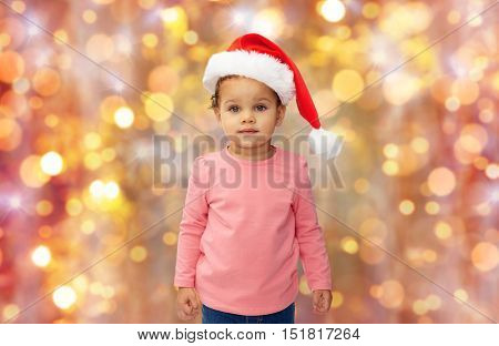 childhood, christmas, holidays and people concept - beautiful little african american baby girl in santa hat over lights background