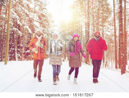 love, christmas, season, friendship and people concept - group of smiling men and women running in winter forest