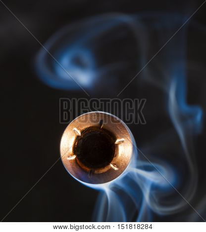 Hollow point handgun bullet with smoke behind pointed at the camera