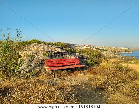 Red bench on the coastline of Peniche, Portugal