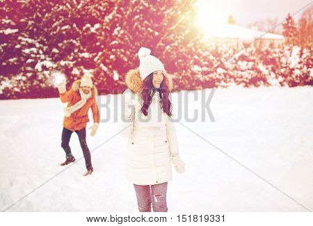 people, season, love and leisure concept - happy couple playing snowballs in winter