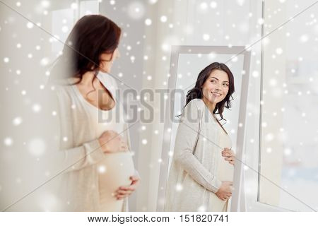 pregnancy, motherhood, people, winter and expectation concept - happy pregnant woman looking to mirror at home over snow