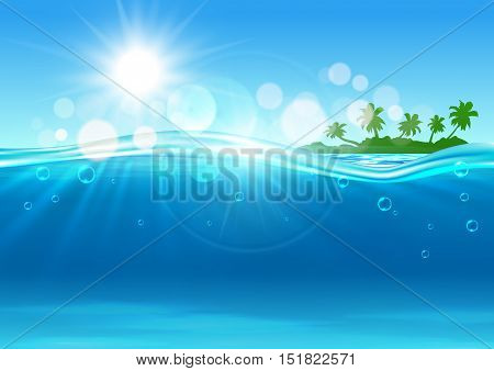 Tropical island background with marine landscape of over and under water surface with green silhouette of island with palms at the horizon and blue waves with sun and flare spots.