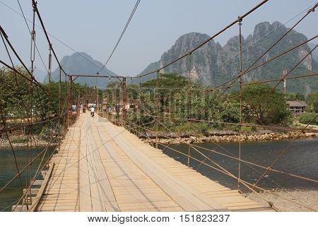 VANG VIENG, LAOS - FEBRUARY 18, 2016: Old chain bridge crossing a river in Vang Vieng on February 18, 2016 in Laos, Asia