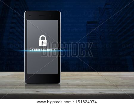 Key icon and cyber security text on modern smart phone screen on wooden table in front of city tower with computer binary code background Cyber security concept