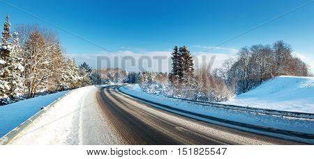 Asphalt road in snowy winter on beautiful frosty sunny day