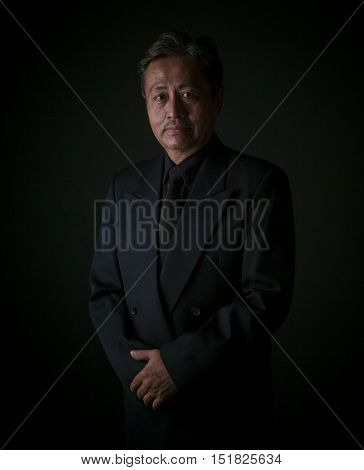 thai senior man wearing black suit sadness emotion portrait by low light photography