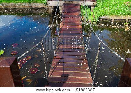 Wooden Bridge over river in spring garden