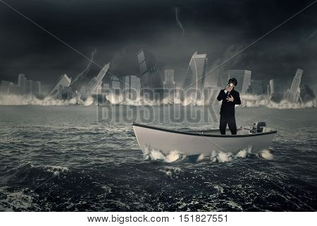Image of a businessman wearing a gas mask and standing in the boat with a town sinking into the sea