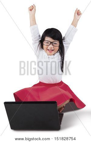 Photo of a cheerful little girl raise hands in the studio while sitting on the floor with notebook computer