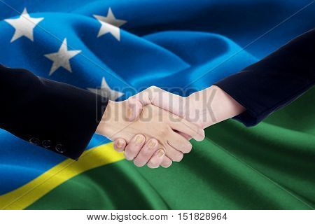 Image of a cooperation handshake with two people hands shaking hands in front of a national flag of Solomon Islands