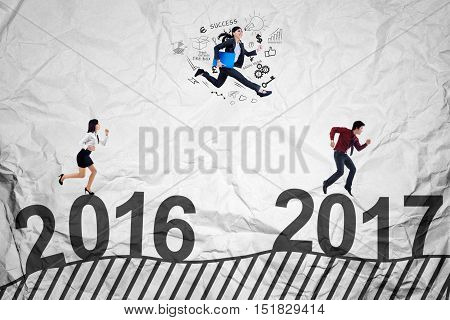 Concept of business competition in 2017 with three young entrepreneurs running and jumping to compete toward 2017