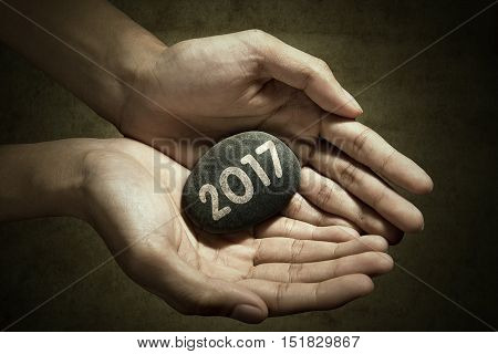 Concept of New Year 2017. Picture of hand holding a stone pebble with number 2017