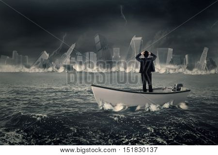 Rear view of lost businessman standing in the boat while looking at a sinking town on the sea