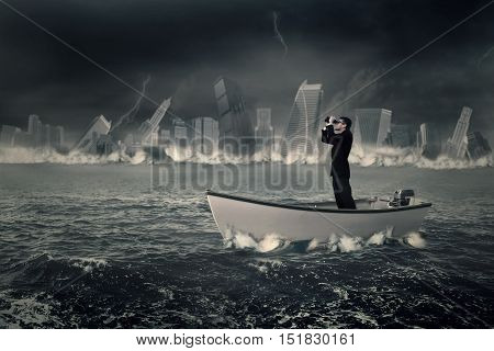 Photo of a male entrepreneur standing on the boat while looking through binoculars with a sinking town at the sea