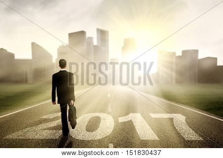 Businesman walking on the street while carrying a briefcase with number 2017 shot in the morning