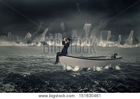 Businessman sitting in a boat while wearing a gas mask and looking through a binoculars on the sea