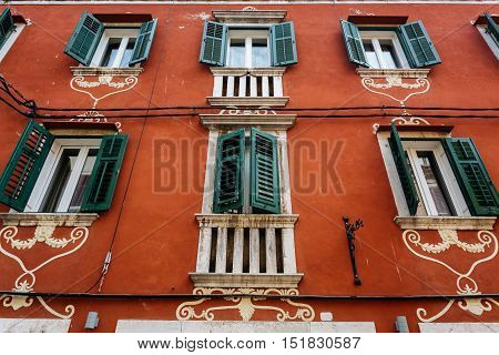 A decorated red house facade with green shutters on the windows in Rovinj, Croatia