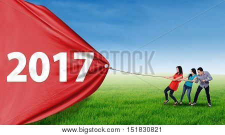 Young Asian people using a rope to pull a big banner with number 2017 on the meadow shot outdoors