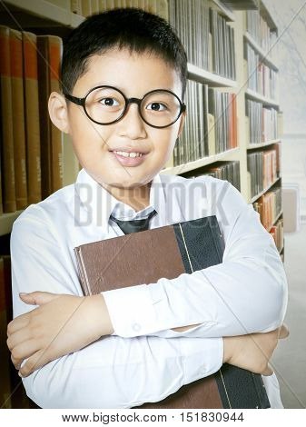 Photo of a schoolboy standing in the library aisle while leaning on the bookcase and holding a book
