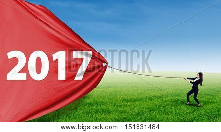 Female entrepreneur using a rope to pull number 2017 on a big banner shot outdoors at field