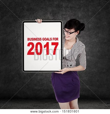 Asian businesswoman holding a whiteboard with business goals for 2017. Concept of business goals in 2017