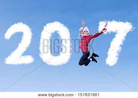 Attractive woman jumping on the blue sky while wearing winter clothes with clouds shaped number 2017
