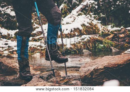 Traveler feet hiking crossing river Travel Lifestyle adventure concept wild nature on background active vacations