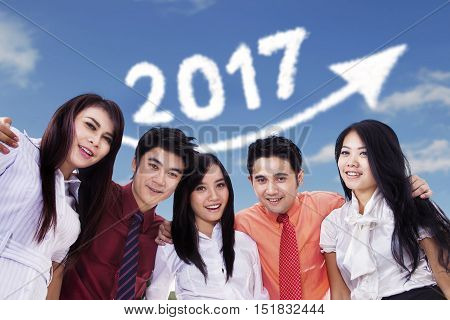 Group of young businesspeople smiling at the camera with upward arrow and number 2017 on the sky